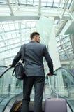 Hombre de negocios en el aeropuerto que va abajo de la escalera móvil Imagenes de archivo