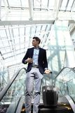 Hombre de negocios en el aeropuerto que va abajo de la escalera móvil Foto de archivo