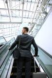 Hombre de negocios en el aeropuerto que va abajo de la escalera móvil Imágenes de archivo libres de regalías