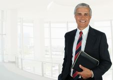 Hombre de negocios en el alto ajuste dominante de la oficina que sostiene un pequeño cuaderno foto de archivo libre de regalías