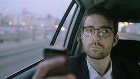 Hombre de negocios en el coche que pone de su teléfono móvil almacen de metraje de vídeo