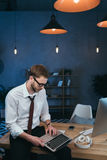 Hombre de negocios en el desgaste formal que trabaja en el ordenador portátil en la oficina moderna Imagen de archivo