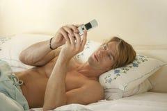 Hombre de negocios en el dormitorio Texting Fotografía de archivo libre de regalías