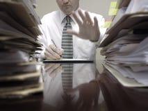 Hombre de negocios en el escritorio con los ficheros que soporta la mano Fotografía de archivo libre de regalías