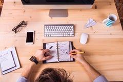 Hombre de negocios en el escritorio, los artilugios de la oficina y las fuentes Imagen de archivo