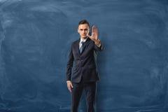 Hombre de negocios en el fondo azul de la pizarra que lleva a cabo una mano en una muestra de la parada Foto de archivo