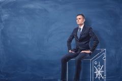Hombre de negocios en el fondo azul de la pizarra que se sienta en una caja fuerte dibujada en blanco imagen de archivo
