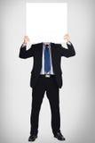 Hombre de negocios en el juego oscuro que lleva a cabo una muestra en blanco Foto de archivo