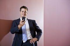 Hombre de negocios en el juego texting en vestíbulo Imagen de archivo