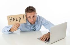 Hombre de negocios en el ordenador portátil y la muestra de la ayuda imagen de archivo