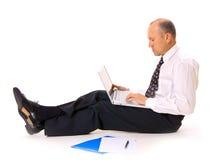 Hombre de negocios en el suelo con la computadora portátil Fotografía de archivo