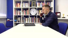 Hombre de negocios en el té de consumición de la oficina almacen de metraje de vídeo