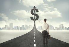 Hombre de negocios en el título del camino hacia una muestra de dólar Foto de archivo