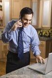 Hombre de negocios en el teléfono celular y la computadora portátil. Fotografía de archivo