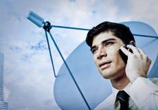 Hombre de negocios en el teléfono móvil con el plato basado en los satélites Fotos de archivo