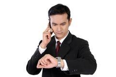 Hombre de negocios en el teléfono que comprueba el tiempo, aislado en blanco Imágenes de archivo libres de regalías