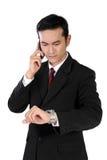 Hombre de negocios en el teléfono que comprueba en su reloj, aislado en blanco Foto de archivo libre de regalías