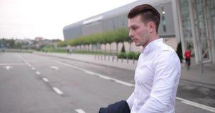 Hombre de negocios en el trabajo El hombre joven hermoso en la camisa blanca camina de un aeropuerto con una maleta y mira alrede almacen de video