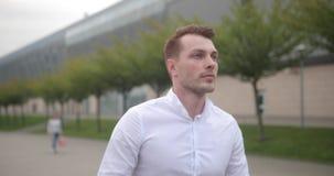 Hombre de negocios en el trabajo El hombre joven hermoso en la camisa blanca camina de un aeropuerto con una maleta y mira alrede almacen de metraje de vídeo