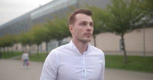 Hombre de negocios en el trabajo El hombre joven hermoso en la camisa blanca camina de un aeropuerto con una maleta y mira alrede metrajes