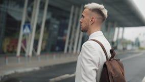 Hombre de negocios en el trabajo Hombre joven hermoso en la camisa blanca que va al aeropuerto con la mochila y que mira en el re almacen de metraje de vídeo