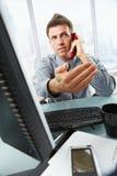 Hombre de negocios en el trabajo que agita de la llamada en oficina imagen de archivo