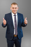 Hombre de negocios en el traje azul que muestra como los fingeres en un backgrou gris imágenes de archivo libres de regalías