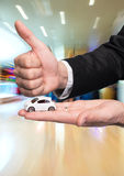 Hombre de negocios en el traje negro que lleva a cabo el pequeño modelo del coche y que muestra muy bien Fotografía de archivo libre de regalías