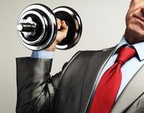 Hombre de negocios en el traje que aumenta pesa de gimnasia Concep de la presión fiscal Foto de archivo
