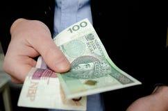 Hombre de negocios en el traje que da el dinero Ciento y veinte zloty polaco, cierre para arriba imagenes de archivo