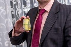 Hombre de negocios en el traje que muestra las ganancias, billetes de banco euro imagen de archivo