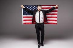 Hombre de negocios en el traje que retiene la bandera de los E.E.U.U. el suyo con la boca abierta imagenes de archivo