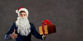 Hombre de negocios en el traje de Santa Claus con un regalo en su mano Foto de archivo libre de regalías