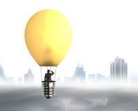Hombre de negocios en el vuelo brillantemente amarillo del globo del aire caliente de la lámpara Foto de archivo libre de regalías