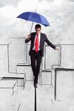 Hombre de negocios en equilibrio sobre ciudad ilustrada Imágenes de archivo libres de regalías