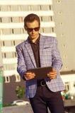 Hombre de negocios en gafas de sol con una tableta en manos imágenes de archivo libres de regalías