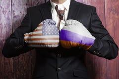 Hombre de negocios en guantes de boxeo con el ruso y la bandera de los E.E.U.U. Los E.E.U.U. contra el concepto de Rusia imágenes de archivo libres de regalías