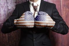 Hombre de negocios en guantes de boxeo con la bandera de los E.E.U.U. foto de archivo