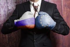 Hombre de negocios en guantes de boxeo con la bandera de unión rusa y europea Rusia contra concepto de la unión europea foto de archivo libre de regalías
