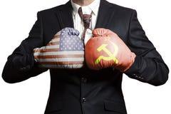 Hombre de negocios en guantes de boxeo con las banderas de los E.E.U.U. y de URSS Los E.E.U.U. contra Concepto de URSS fotografía de archivo libre de regalías