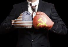 Hombre de negocios en guantes de boxeo con las banderas de los E.E.U.U. y de URSS Los E.E.U.U. contra Concepto de URSS imagen de archivo libre de regalías