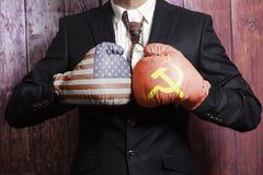 Hombre de negocios en guantes de boxeo con las banderas de los E.E.U.U. y de URSS Los E.E.U.U. contra Concepto de URSS imagenes de archivo
