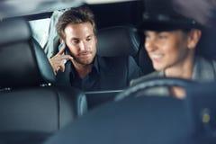 Hombre de negocios en la conducción del chófer de la limusina Foto de archivo