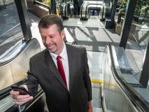 Hombre de negocios en la escalera móvil con Smartphone imágenes de archivo libres de regalías