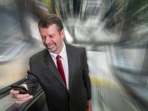 Hombre de negocios en la escalera móvil con Smartphone y la falta de definición de movimiento Foto de archivo libre de regalías