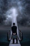 Hombre de negocios en la escalera móvil debajo de las nubes Imagen de archivo