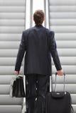 Hombre de negocios en la escalera móvil con el bolso y la carretilla Imagen de archivo