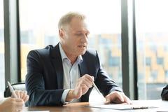Hombre de negocios en la mesa de reuniones Fotografía de archivo libre de regalías