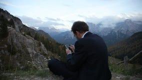 Hombre de negocios en la montaña que envía el mensaje de texto que toma la imagen almacen de metraje de vídeo