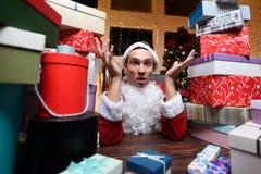 Hombre de negocios en la oficina en el ` s Eve del Año Nuevo Él lleva el traje de Santa Claus Alrededor de él muchos regalos, Foto de archivo libre de regalías